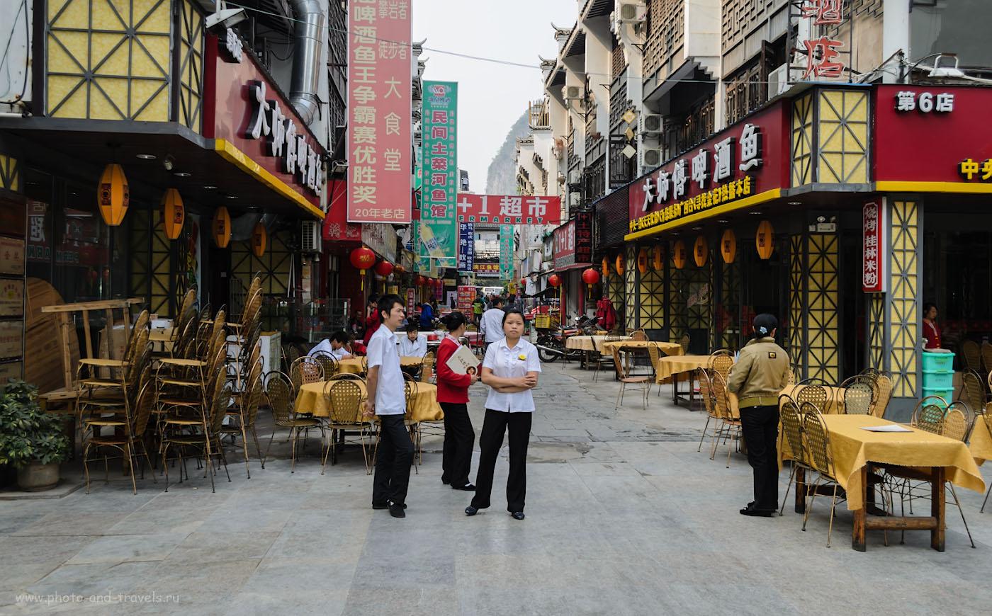 Фото 1. Квартал с ресторанами для туристов в деревне Яншо (Yangshuo). Мы ели в другом месте. Отзыв о путешествии по Китаю самостоятельно. Все фото сняты на любительскую зеркалку Nikon D5100 KIT 18-55. Настройки: 1/200 сек., диафрагма f/5.0, ISO 100, фокусное расстояние 18 мм.