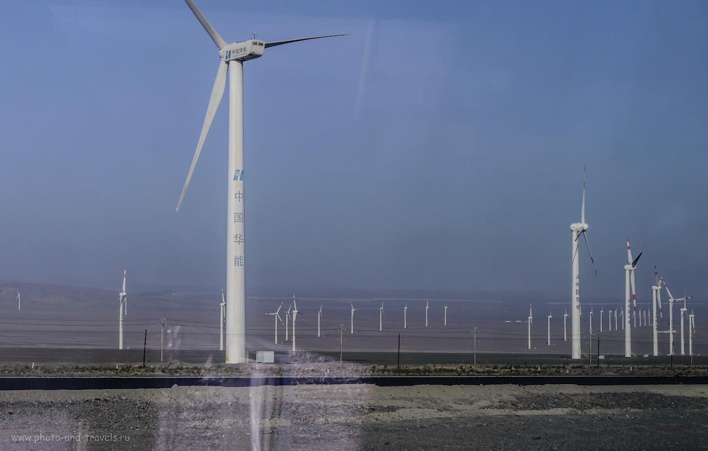 Фото 3. Ветряки крупнейшей в Азии ветряной электростанции Дабанчэнь. Ряды электрогенераторов тянутся на сотни километров пустыни вдоль трассы. Снято в движении через окно автобуса. Поездка из Урумчи в Турфан по время путешествия по Китаю. 1/800, 9.0, 200, 62.