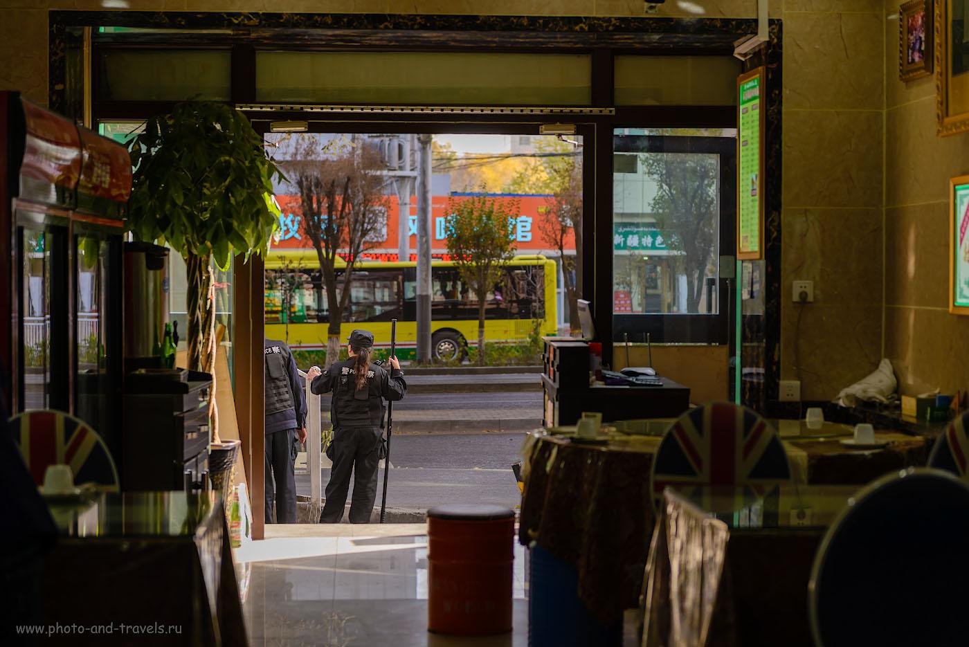 Фото 28. Женщина-полицейский с копьем-электрошокером. Снято из кафе в Урумчи. 1/160, 2.8, 125, 70.