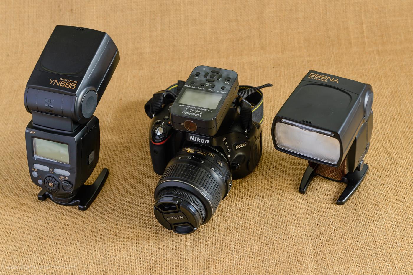Фото 1. Любительская зеркалка Nikon D5100 KIT 18-55 VR с установленным на ней трансмиттером Yongnuo YN-622N-TX. Внешние вспышки YongnuoYN685N по размерам сопоставимы с кропнутой тушкой. Снято на полный кадр Nikon D610 + объектив Nikon 24-70mm f/2.8 при естественном свете от окна. Слева – белый отражатель. Штатив Sirui T-2204X с головой Sirui G-20KX. Настройки: В=1,6 секунды, +1.0 EV, f/8.0, ISO 200, ФР=56 мм.