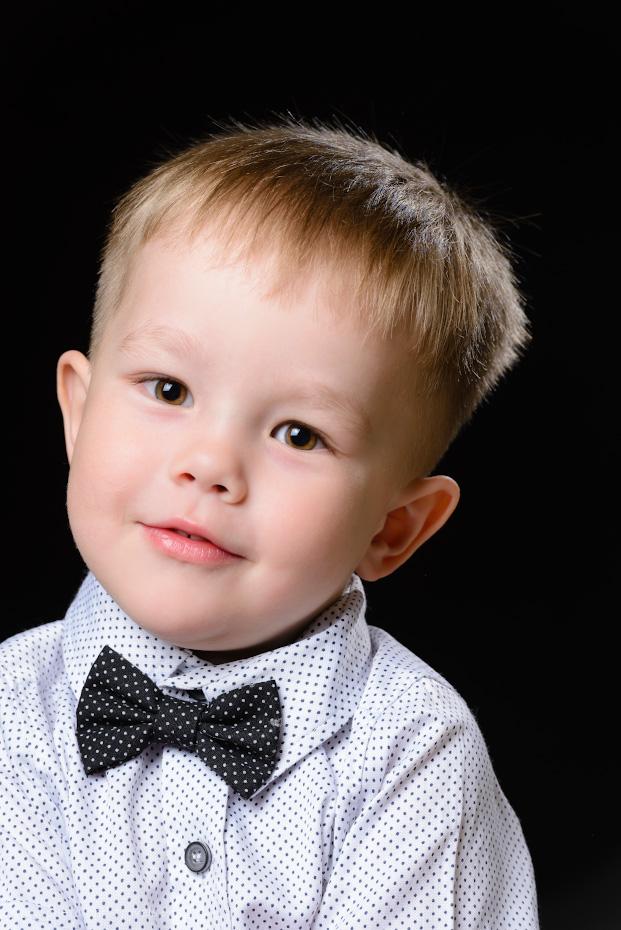 Пример съемки детского портрета в квартире. Камера – Nikon D610, объектив Nikon 70-200mm f/2.8G. Рисующий свет – вспышка Yongnuo YN-685 в софтбоксе Godox, контровый – голая YN-685. Фон – отрез черной ткани. Настройки: 1/200, 9.0, 500, +0.67, 185.