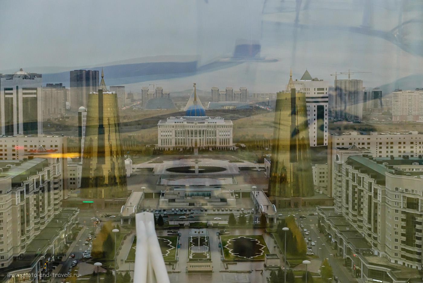 Фото 6. Вид на резиденцию президента «Ак Орда» со смотровой площадки внутри шара монумента «Байтерек». Вдали – пирамида Дворца мира и согласия и Дворец независимости, а также дворец творчества «Шабыт». Отзыв об экскурсии по достопримечательностям Астаны за полдня. 1/160, +0.33, 4.0, 4000, 70.