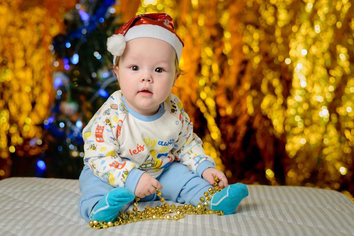 Фото 32. Новогодняя фотосессия с ребенком 6 месяцев. Снято на зеркалку Nikon D610 и портретный фикс Nikon 50mm f/1.8G. Освещение от одной внешней вспышки Yongnuo YN-685N, установленной на стойке «Viltrox» слева. Справа – белый отражатель. Вторая вспышка YN-685N светит на фон. Параметры: 1/200, 2.8, 160, 50.