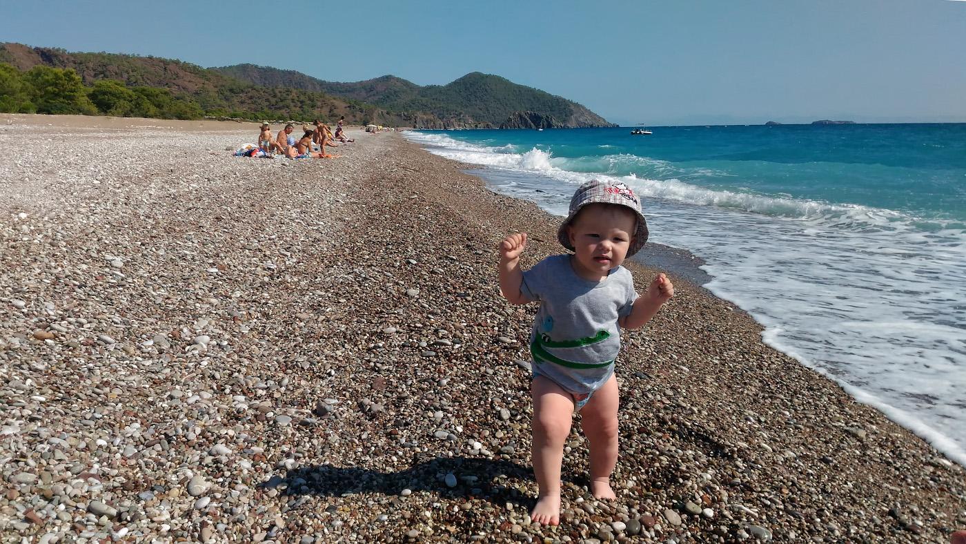 Фотография 32. Если на море будут волны, с маленьким ребенком не покупаешься. В дали на заднем плане - скала Карабурун (Karaburun), что находится в северной части пляжа Чиралы. Снято на смартфон.
