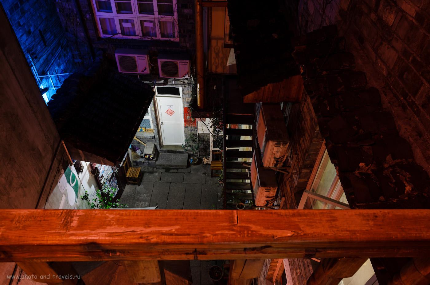 11. Советую, где поселиться в городе Фэнхуан. Дворик нашего хостела. Всё красное, так как слева у фотографа - красный китайский фонарик. Как мы доехали из Zhangjiajie в Fenghuang Ancient Town на автобусе. Настройки: В=30 сек., f/10. ISO 100, ФР=17 мм.